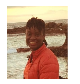 Dr. Ibukun Akinrinade pose in front of a beach. She wears an orange jacket.